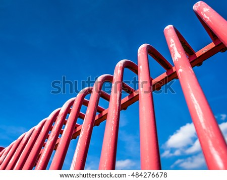 Red metal barred modern security barrier against a blue sky.