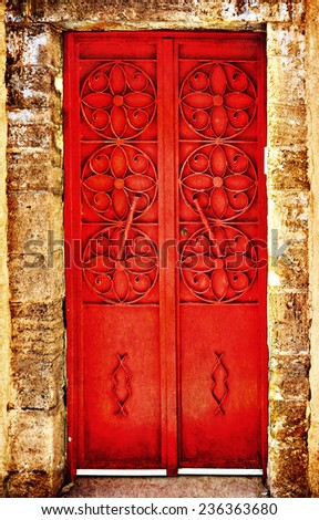Red metal forged door of sandstone traditional building, Middle east. Architectural theme. Photo in retro style. Paper texture. Aged textured photo in retro style  - stock photo