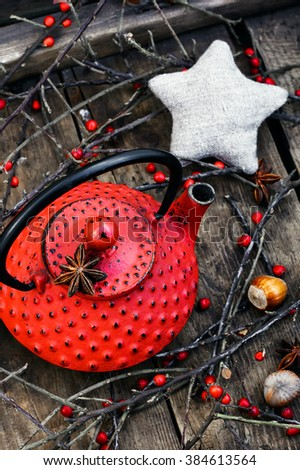 Red metal kettle,branches with berries on wooden background - stock photo