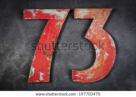Red metal number seventy-three on a the wall - stock photo