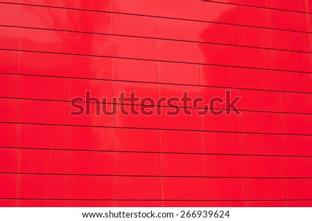 Red metal panel wall of contemporary office building facade closeup as background - stock photo