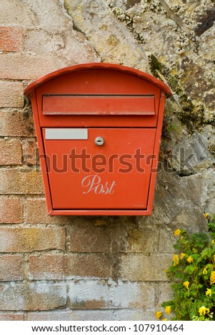 Red metal post box on an old brick wall - stock photo