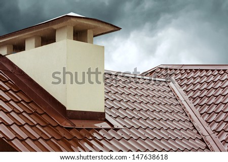 Red metal roof tile and smokestack - stock photo