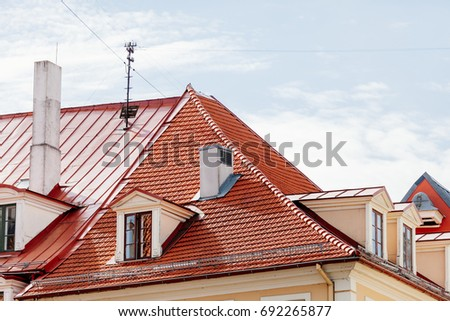 Red metal roof with windows and chimney in old town