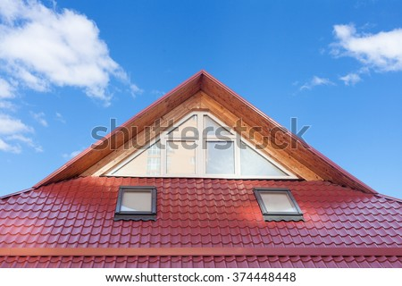 Red Metal tiled Roof with New Dormers, Roof Windows, Skylights and Roof Protection from Snow Board - stock photo