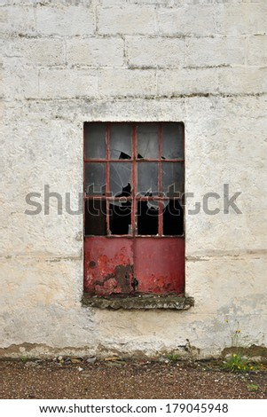 Red metal window frame with broken glass in a white stone wall - stock photo