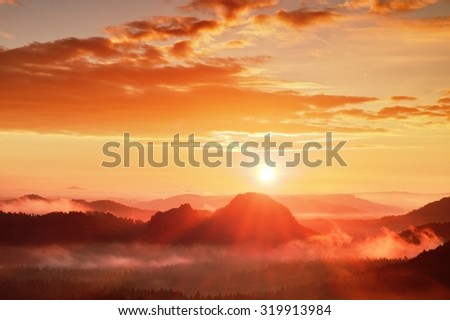 Red misty daybreak. Foggy autumn morning in a beautiful hills. Peaks of hills are sticking out from foggy background, the fog is red and orange due to Sun rays.