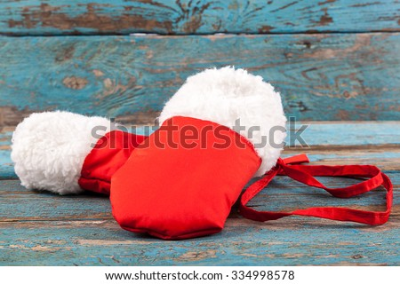 Red mittens with fur on painted blue wooden boards. - stock photo