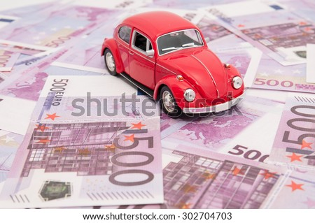 Red model car on banknotes, symbolic photo for car buying,