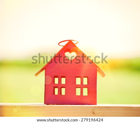 red model of house as symbol on sunlight background - stock photo