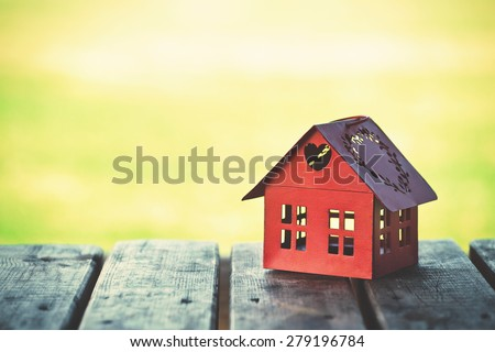 red model of house as symbol on sunny background - stock photo