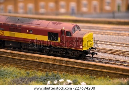 Red model train diesel railway engine. A weathered red yellow liveried british diesel electric locomotive parked on a model railway layout with several railroad tracks visible. - stock photo