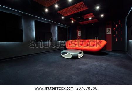Red modern sofa in dark living room - stock photo