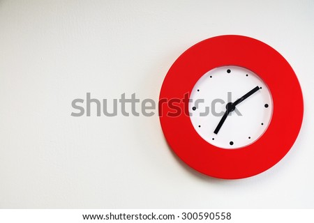 Red modern wall clock on white concrete wall - stock photo