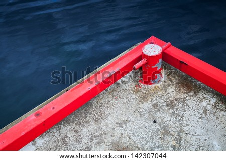 Red mooring bollard on concrete pier