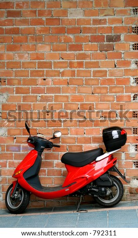 Red moped or motorbike resting or leaning against a brick wall in the backstreets on Marbella in Spain - stock photo