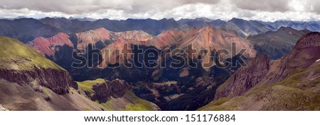 Red Mountain Range Ouray Colorado. These 'red' mountains are the result of a heavy concentration of iron ore. This scene has sheer cliff faces, mountain peaks in the distance and a mining operation. - stock photo