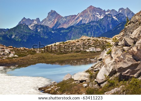 Red Mountains Small Blue Snow Pond Artist Point Mount Baker Highway Green Grass Heather - stock photo