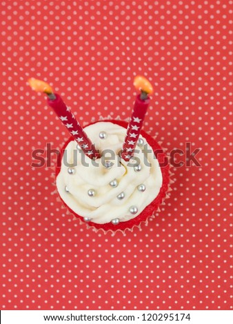 red muffin on red background with white polka dots with two candles seen from above - stock photo