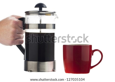 Red mug and coffee pot holding by the human hand - stock photo