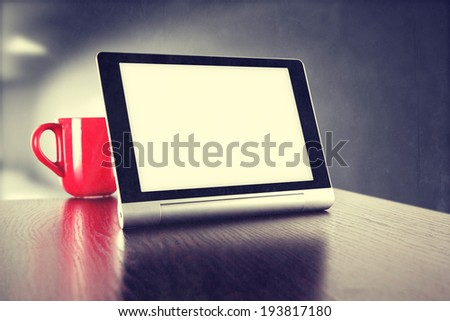 red mug desk in office and tablet  - stock photo
