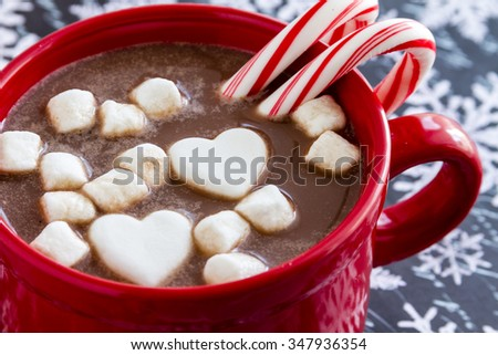 Red mug filled with hot chocolate with heart shaped marshmallows, peppermint candy canes on black and white snowflake background - stock photo