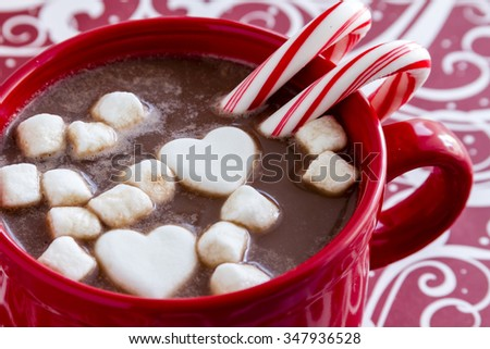 Red mug filled with hot chocolate with heart shaped marshmallows, peppermint candy canes on red swirled background - stock photo