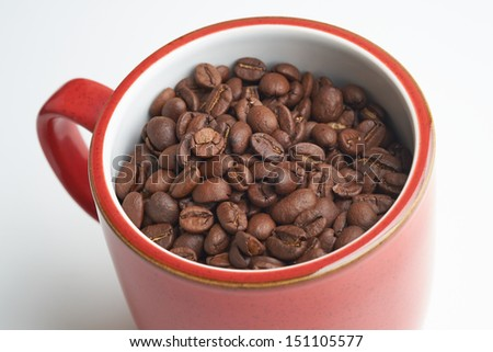 Red mug with coffee beans in it on a white isolated background.