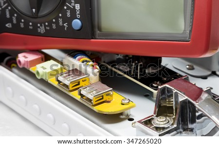 Red multimeter on printed-circuit board. Measurements in electrical instruments. - stock photo