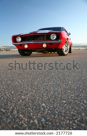 red muscle car camaro and asphalt at ground level - stock photo