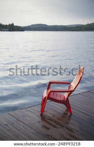 Red Muskoka Chair Sitting on Dock by Lake - stock photo