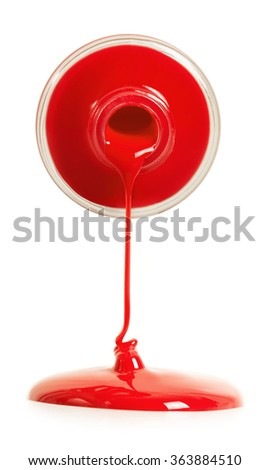 Red nail polish pouring from a bottle - stock photo