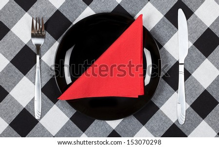 Red napkin on black plate.