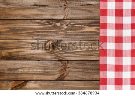 Red napkin on the old wooden table. - stock photo