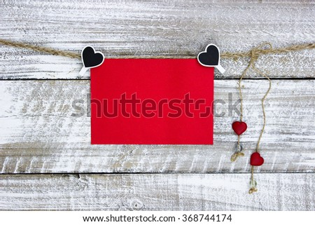 Red note card hanging on clothesline with hearts and white rustic antique wood background; Valentine's Day and love concept - stock photo
