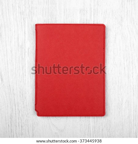red notebook on white wooden table, top view