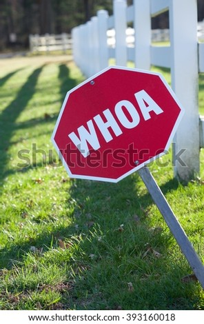 """RED OCTAGON """"WHOA"""" (STOP) SING IN FRONT OF HORSE FARM WITH WHITE FENCE  - stock photo"""