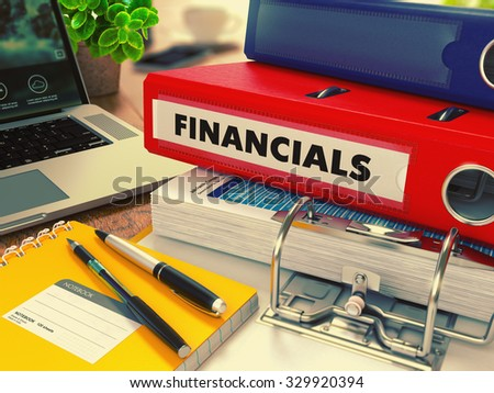 Red Office Folder with Inscription Financials on Office Desktop with Office Supplies and Modern Laptop. Business Concept on Blurred Background. Toned Image. - stock photo