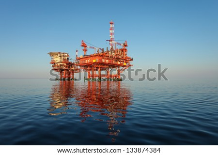 red oil rig platform on calm blue sea - stock photo