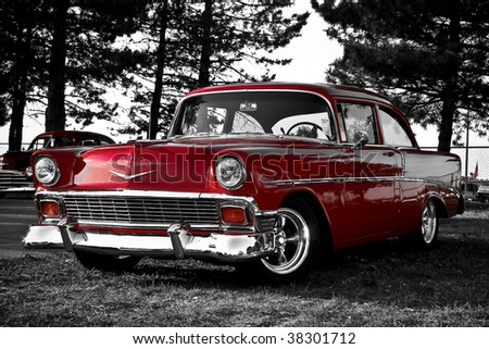 red old car parked in front on trees - stock photo