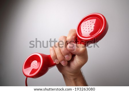 Red old fashioned telephone receiver on gray background concept for customer support line or important call  - stock photo