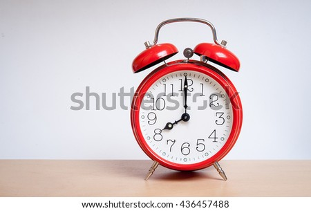 red old retro style alarm clock on wood table. Alarm clock shows eight o`clock