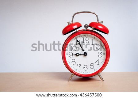 red old retro style alarm clock on wood table. Alarm clock shows five minutes to nine o`clock