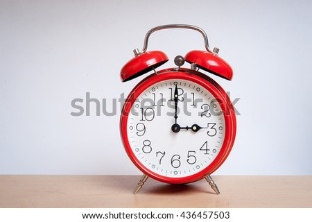 red old retro style alarm clock on wood table. Alarm clock shows three o`clock