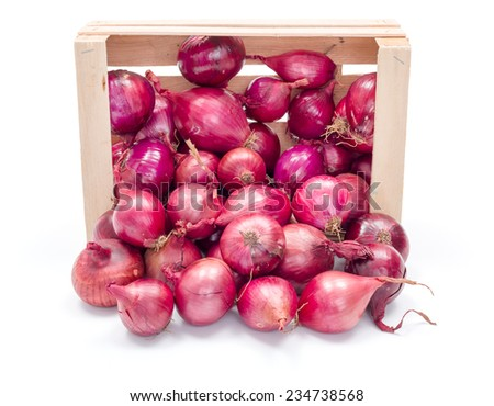 Red onion bulbs spreading out from wooden crate - stock photo