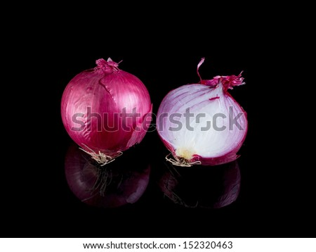 Red onion isolated on black background with reflection.