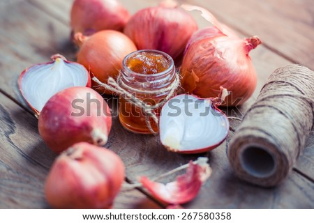 Red onion marmalade in a small glass jar on wooden table - stock photo