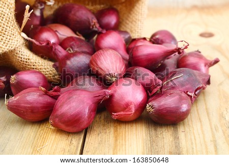 Red onions isolated in burlap on wooden background  - stock photo
