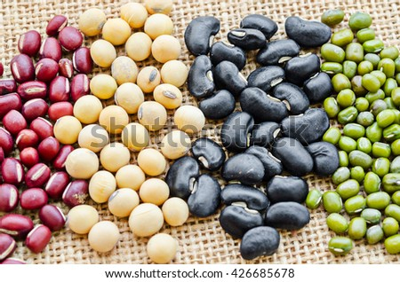 Red or azuki bean, yellow or soy bean, black bean and green or mung bean on sack background. - stock photo