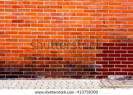 red orange brick wall with pavement